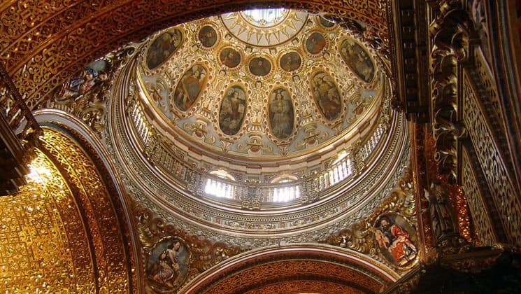 looking up at the inside of an ornate basilica dome on the quito and guayaquil galapagos land tour