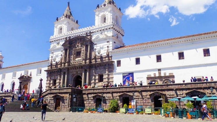 front of a white museum on a sunny day with clouds above on the quito and guayaquil galapagos land tour