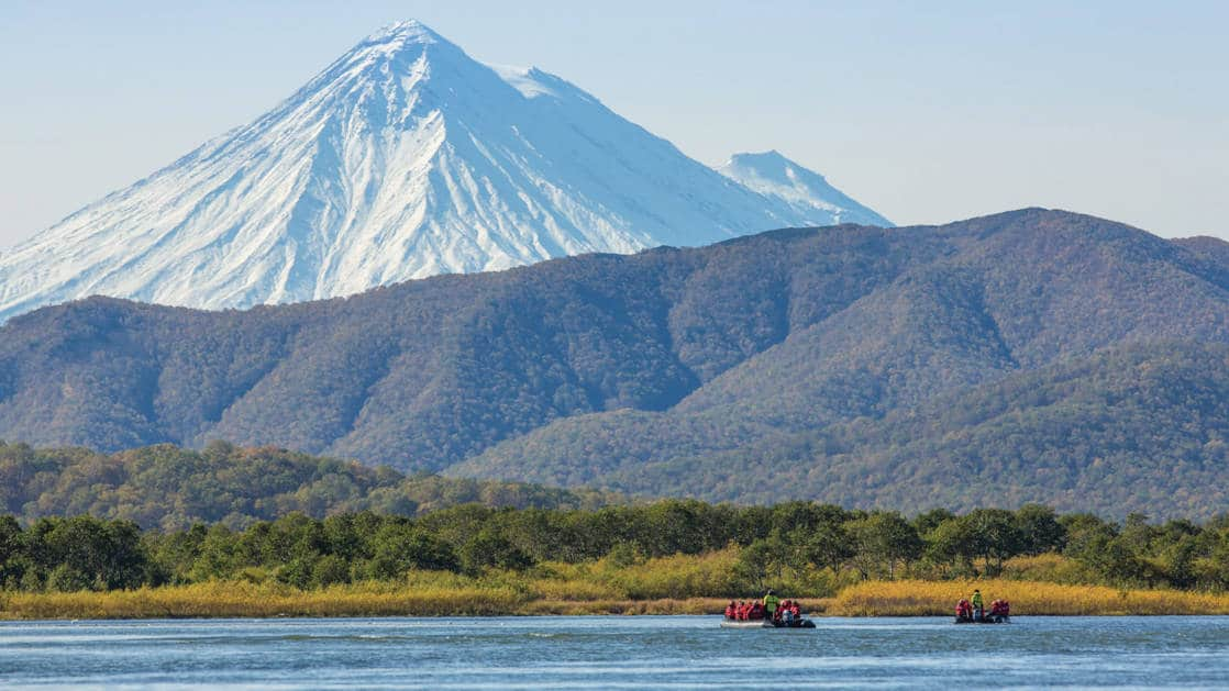 three groups of travelers take kodiac rides on the Zhupanova River, Russia. A jagged snow mountainrnage in the distance behind a lower forested mountain, seen on Across the Bering Sea Cruise