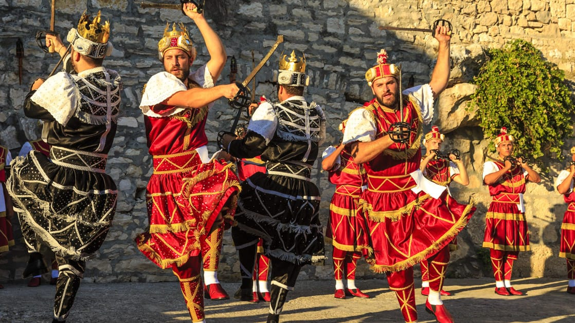 A group of men sword dancing in Old Town Korcula, as seen from the under sail small ship cruise from Greece to the Dalmatian coast