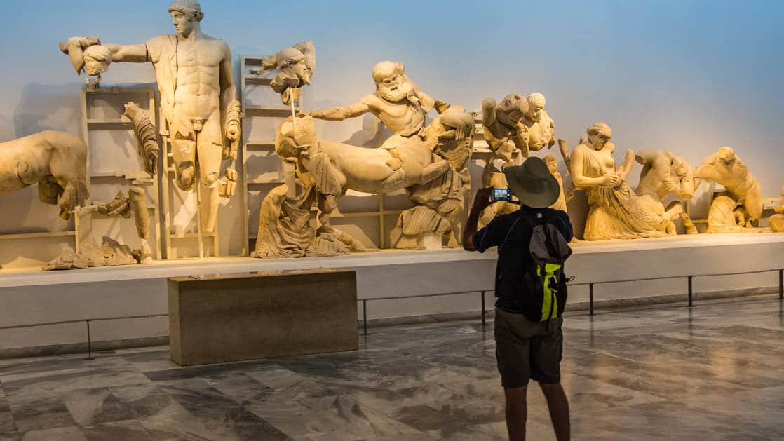 a male guest taking photos of statues in museum of Olympia Archaeological Site, Greece, seen from the under sail small ship cruise from Greece to the Dalmatian coast
