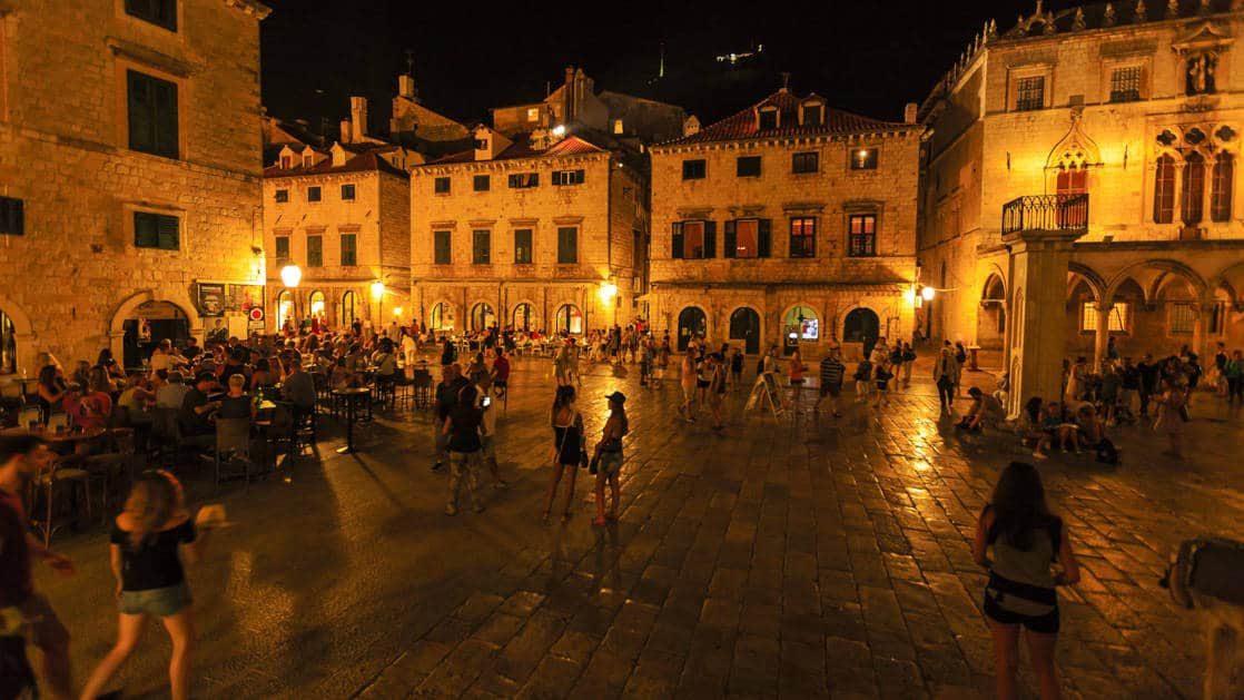 Historic Old Town of Dubrovnik, Croatia at night. Glowing street lights light up a busy street square seen on the under sail small ship cruise from Greece to the Dalmatian coast