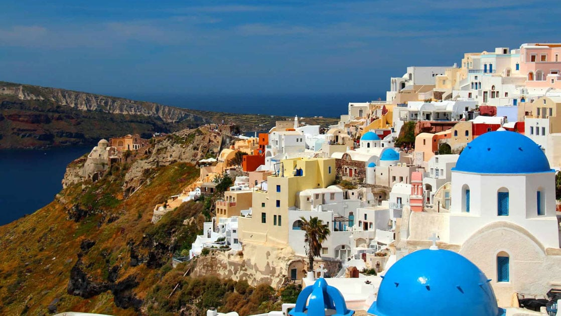 The view of santorini's blue domes and white architecture along the bluffs above the mediterranean as seen from the small ship cruise sailing the greek isles