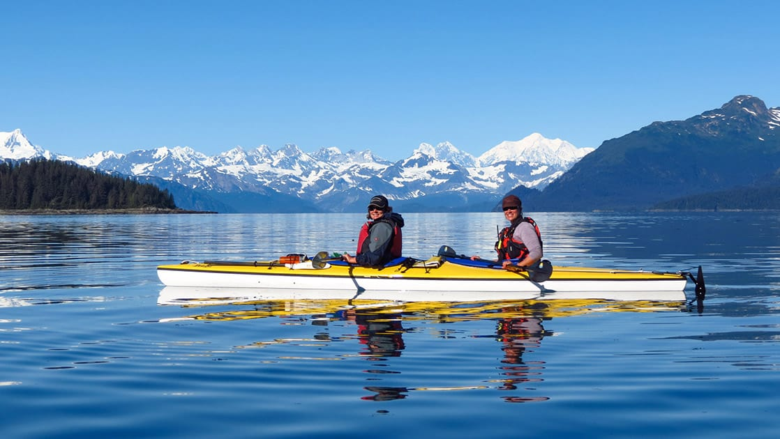 adventure travelers in a yellow kayak paddle on calm water on a sunny day in alaska with snowy mountains in the distance