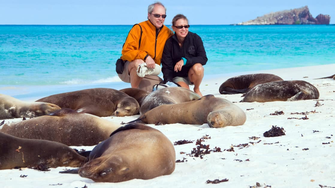 a man and a woman crouch low to pose for a photograph with the sea lions asleep on a white sand beach with turquoise water in the background at the Galapagos islands