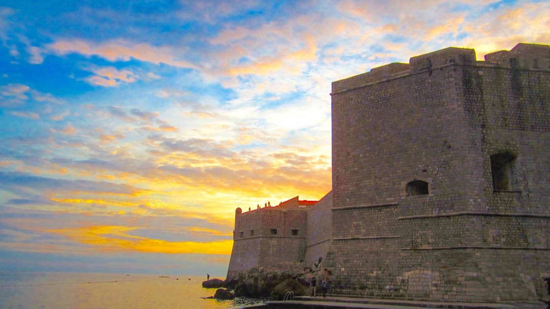 A castle along the water with high walls in a croatian town at sunset