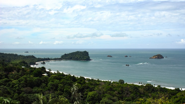 A view of a calm bay in Costa Rica with white-sand beaches and an island.