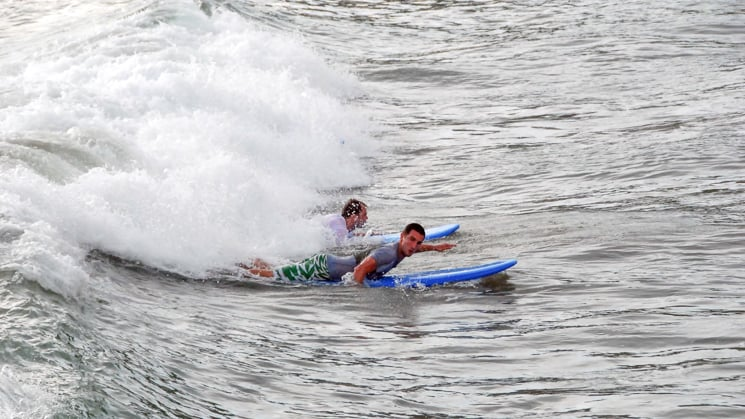 Surf lessons in Costa Rica with two surfers on their stomachs on a wave.