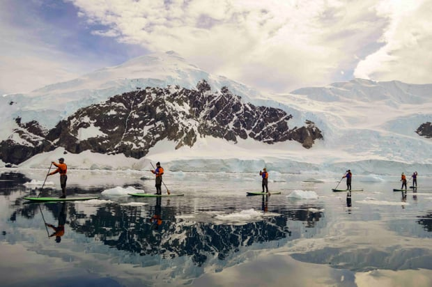 A group of people stand-up paddleboarding among floating ice in Antarctica.
