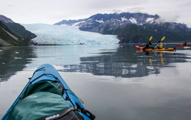 Guests on small ship cruise in Alaska kayak by glaciers on excursion in Kenai Fjords National Park.