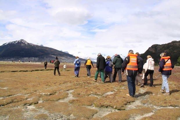 Group of Patagonia travelers hiking on tidal flats with mountains.