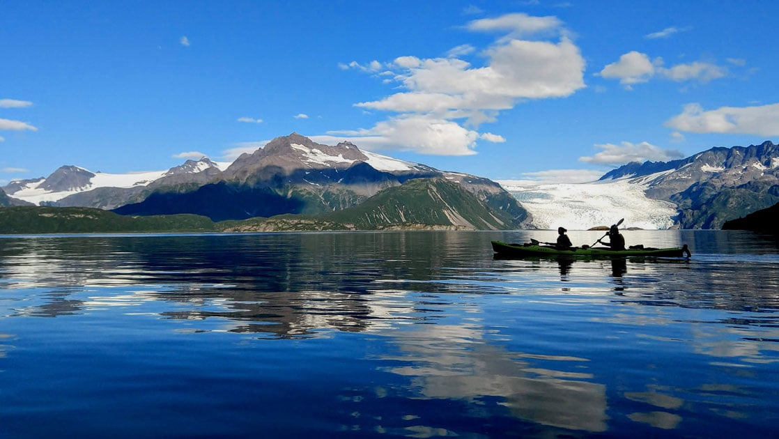 Tandem kayakers paddle glassy water backed by a white glacier & green hills under a blue sky on the Alaska Coast to Denali Journey.