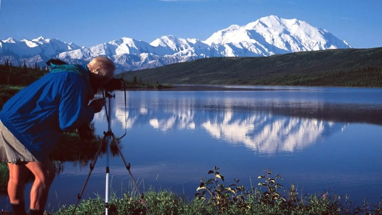 photographer setting up shot by lake with distant mountains on alaska coast to denali journey