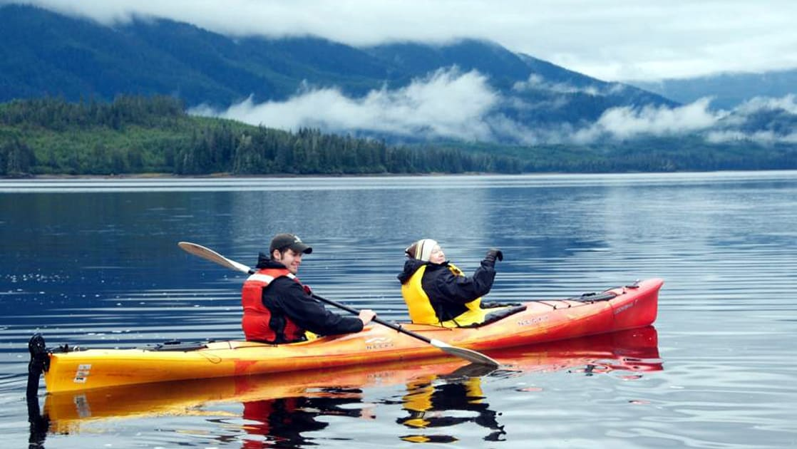 tandem kayak paddling in a calm bay in alaska with low misty clouds
