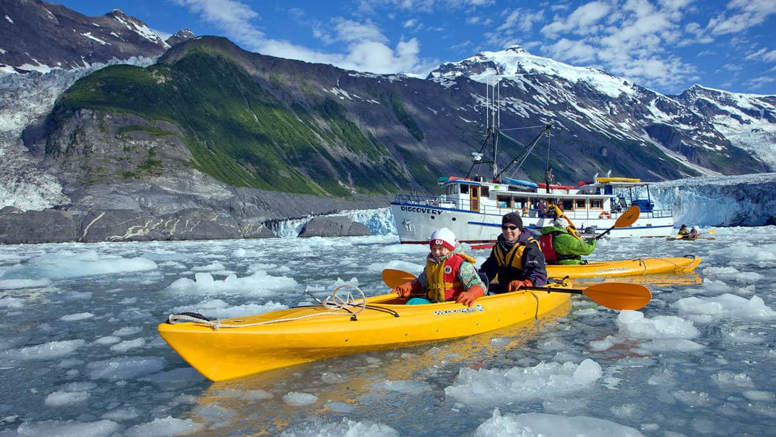Guests on the MV Discovery, enjoy a kayak excursion in the iceberg filled waters of Barry Arm, Chugach mountains in Alaska with their small ship behind them