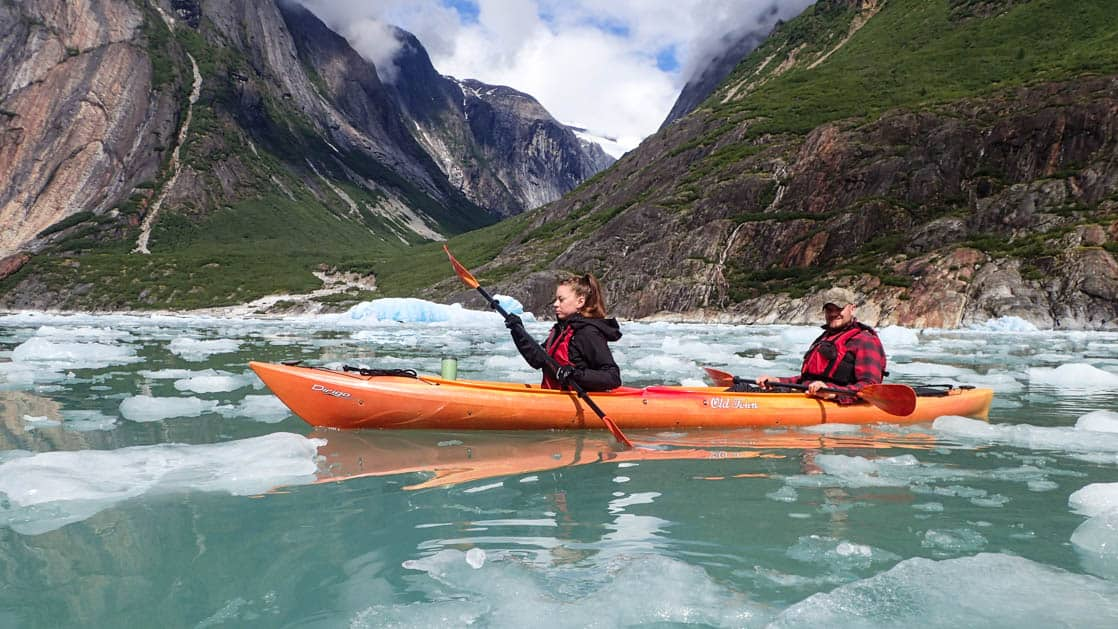 Kayakers rowing through the fjords with icebergs in Alaska.
