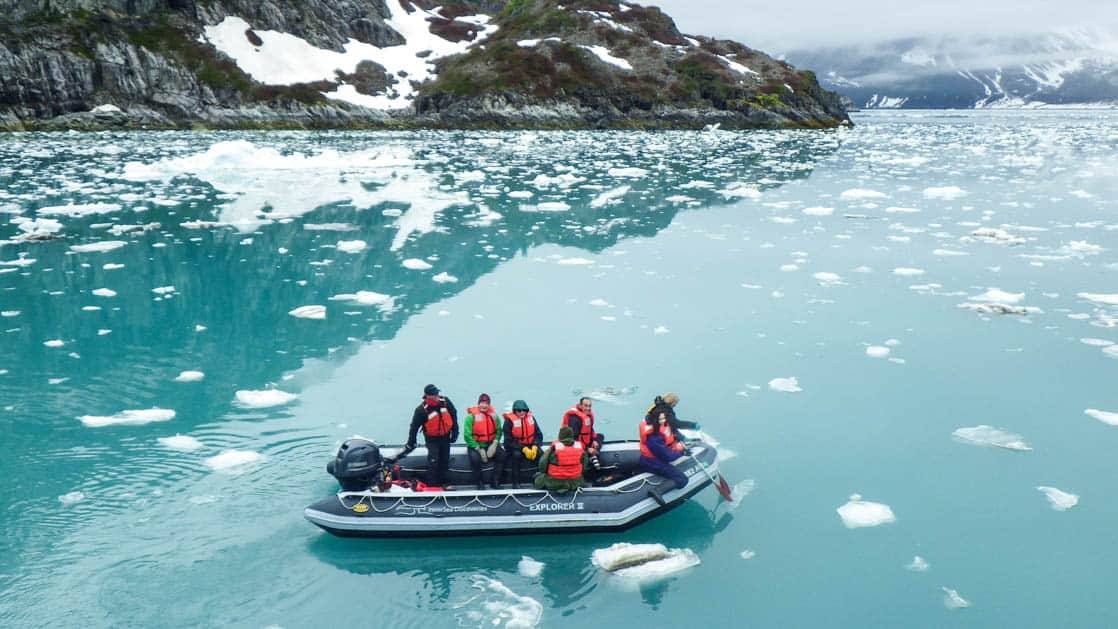 Guests floating in skiff surrounded by ice bergs in a fjord in Alaska.