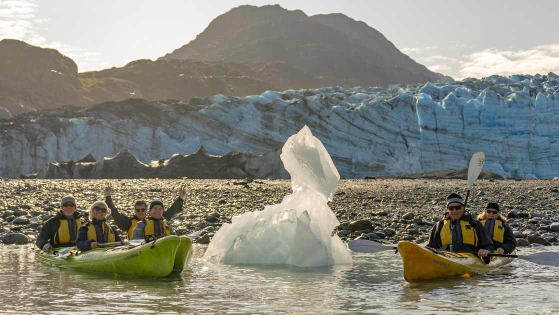 In Alaska a group of kayakers float in green and yellow kayaks next to a white iceberg and in front of an icy teal glacier.