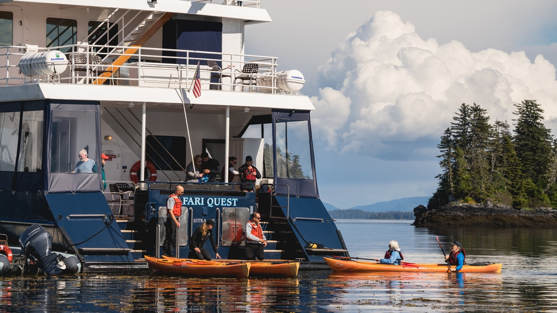 The safari quest Alaska small ship floats as guests return from a kayak activity, the crew on board waiting to help them disembark.