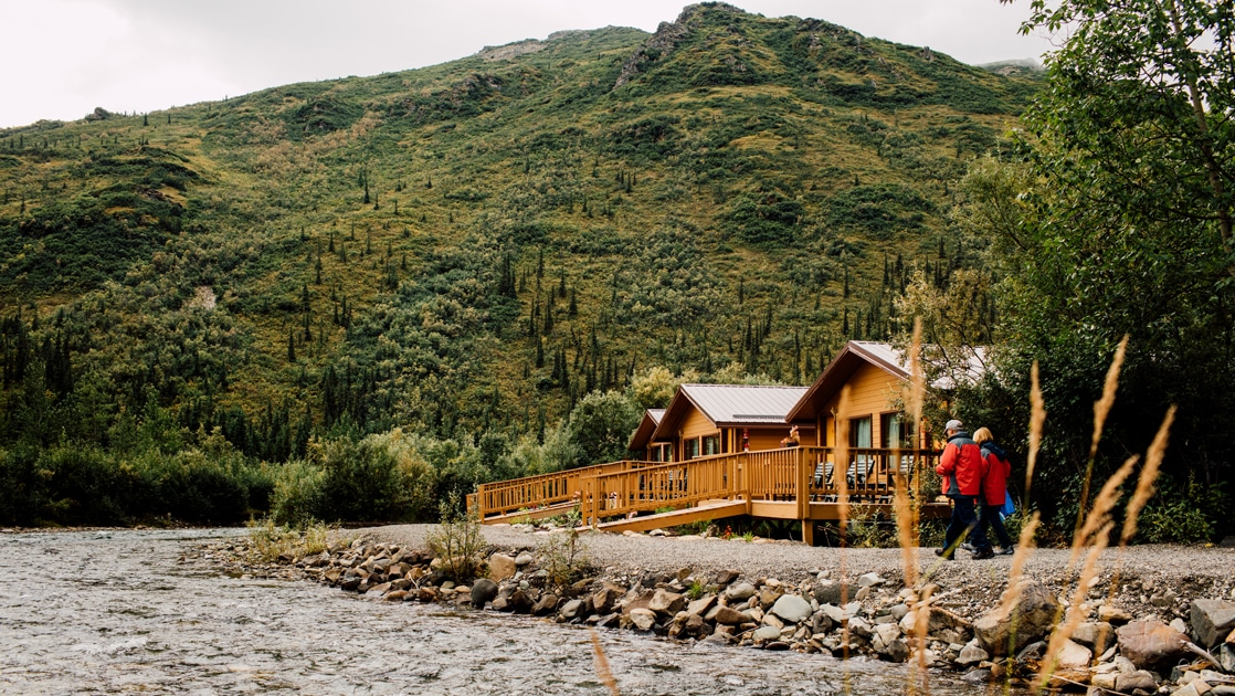A couple wearing red parkas walk on a rocky rover shoreline towards brown wooden cabins set against a lush green mountainside in Denali.