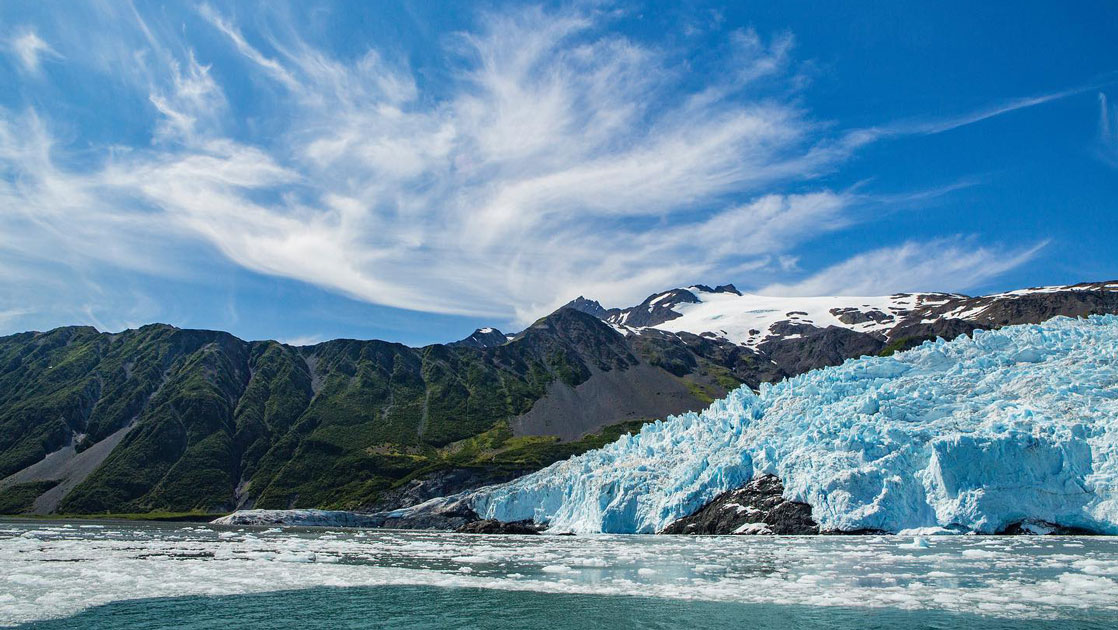 Icy blue glacier leads into a body of water beside green mountains under a blue sky on the Alaska Grand Adventure.