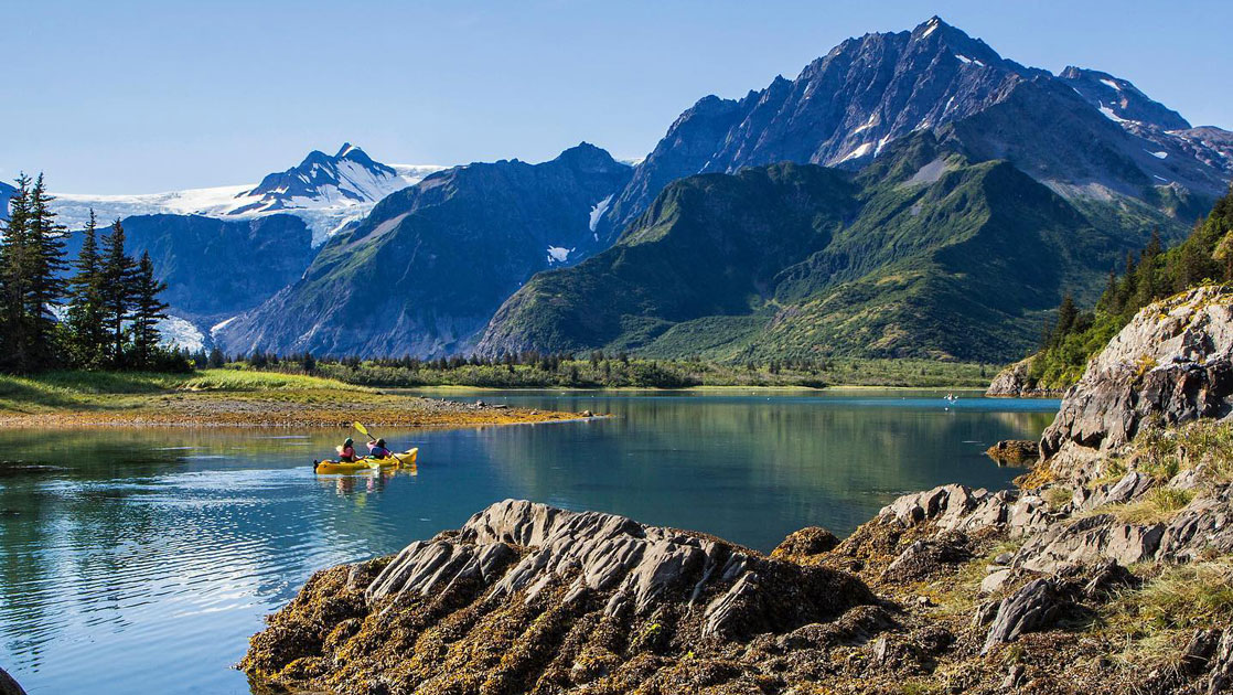 Tandem kayakers paddle glassy waters at Pedersen Lagoon, beside rocky shoreline & craggy green mountains on the Alaska Grand Adventure.