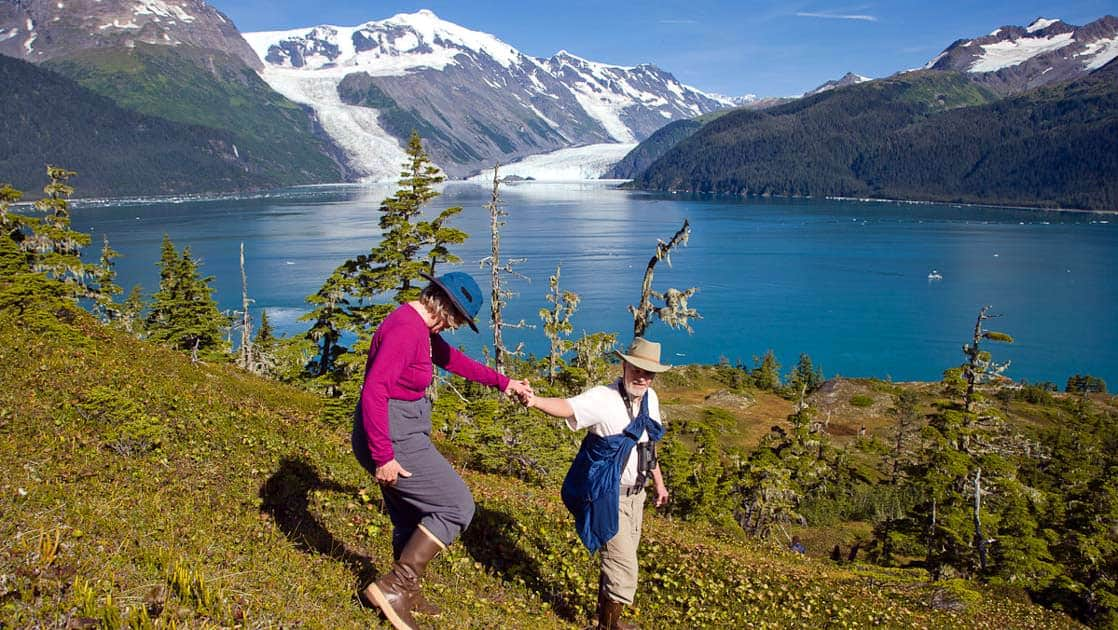 A couple hiking Mount Gilbert and Mount Gannet of the Chugach mountains, with the Cascade and Barry glaciers flowing into Barry Arm