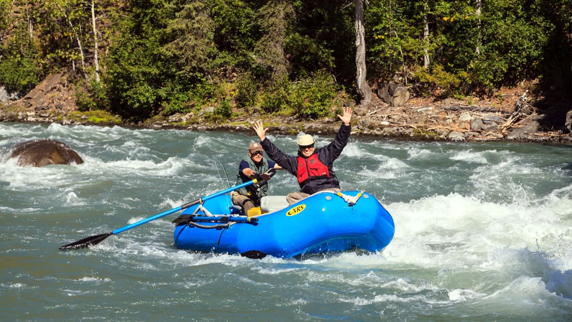 man with his arms up in the air at the front of a raft going down a river in alaska with his guide holding the paddles