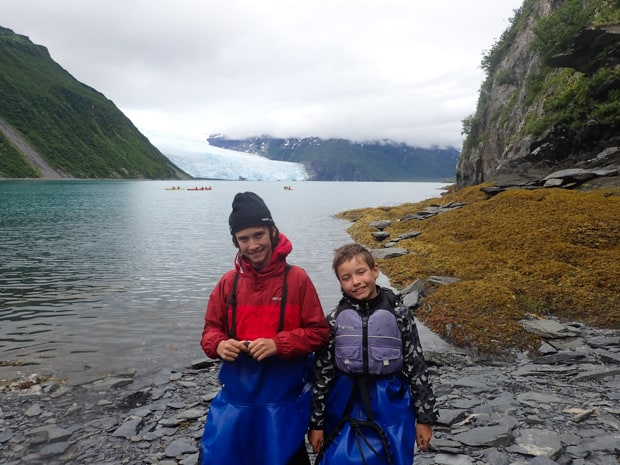 Two young boys wearing kayak skirts smiling at the camera in a bay with kayakers and a glacier behind them.