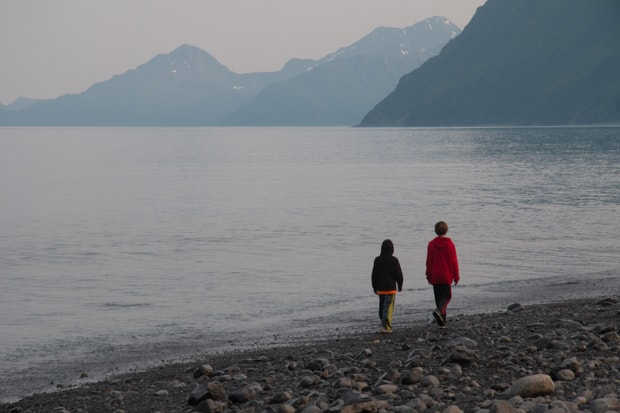 Two young boys walking along a beach in Alaska with mountains in the background.