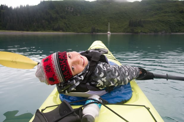One kid in the front of a yellow kayak laying back and looking back while kayaking through Alaska.