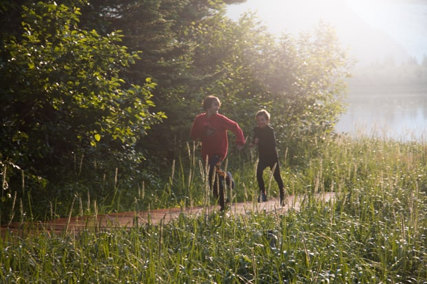 Two kids racing along a path in Alaska having fun while on a land tour.