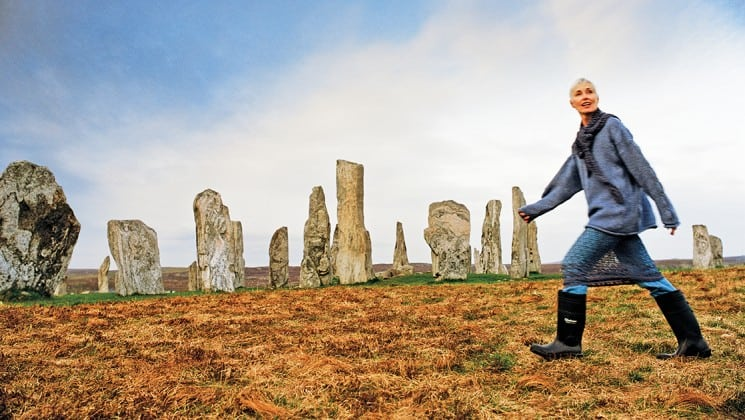 Woman walking with high rubber boots in the field around the Callanish Stone monuments behind her on the outer hebrides of scotland
