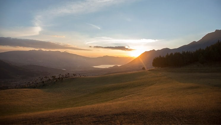 The sun it setting over the mountain range on Ecuador's Andes, rolling hills open field and a lake are glowing.