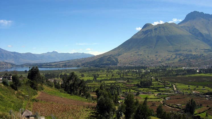 village at base of mountain beside water on andes highland haciendas land tour
