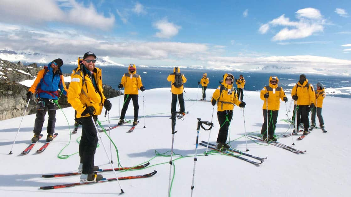 antarctic explorer small ship cruise travelers with yellow jackets standing with cross country skis on