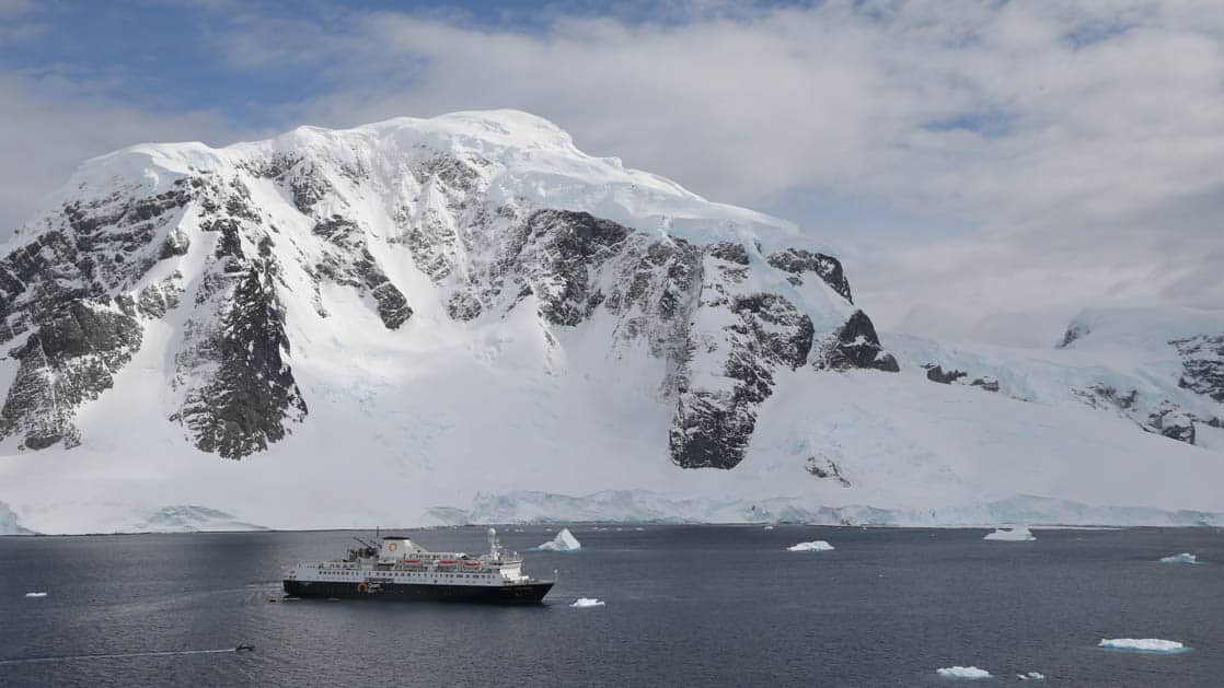 ocean endeavour antarctic expedition ship cruises on an overcast day with a large snowy mountain behind it