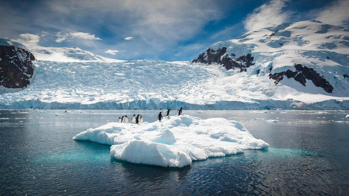 a group of penguins standing on a floating iceberg in the antarctic ocean on a mostly sunny day with mountains behind them