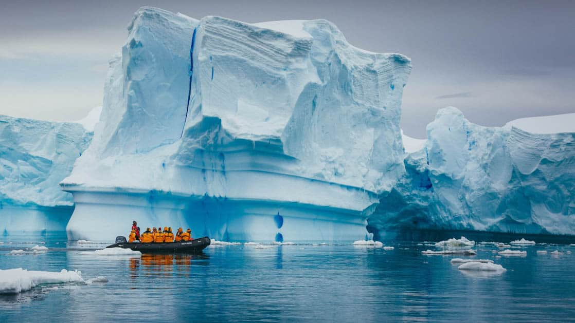 adventure travelers wearing yellow jackets in a zodiac skiff cruise in front of a large iceberg on an overcast day in antarctica