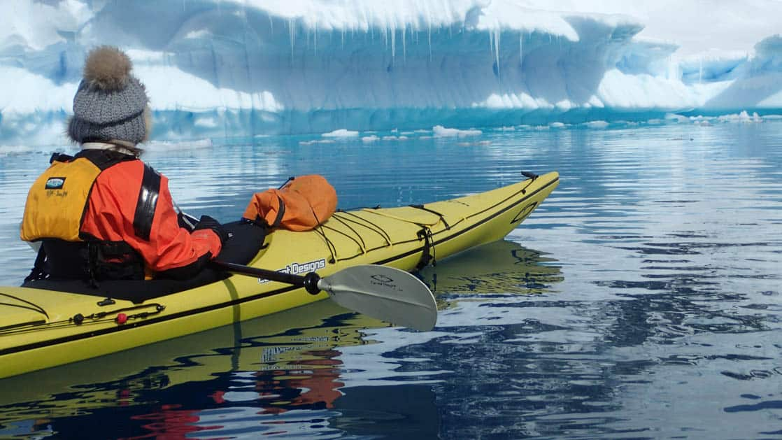 adventure traveler in a yellow kayak sits in calm water looking at an iceberg on the antarctic explorer small ship cruise trip