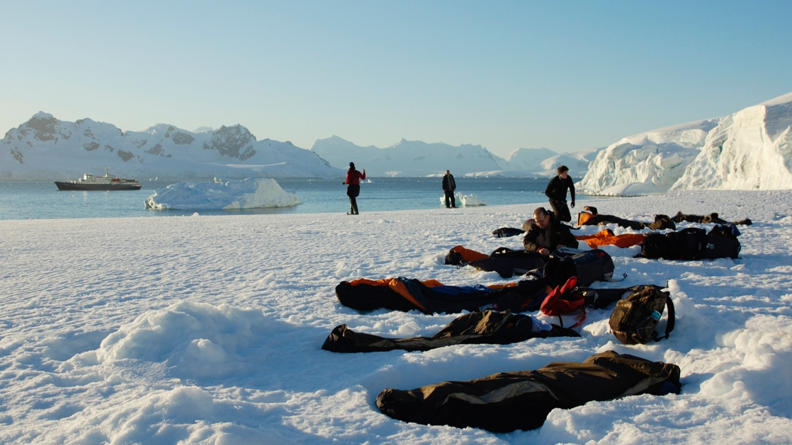 Sleeping bags in bivvy sacks at sunset lay atop Antarctica's snow-covered landscape with a small ship in the background.