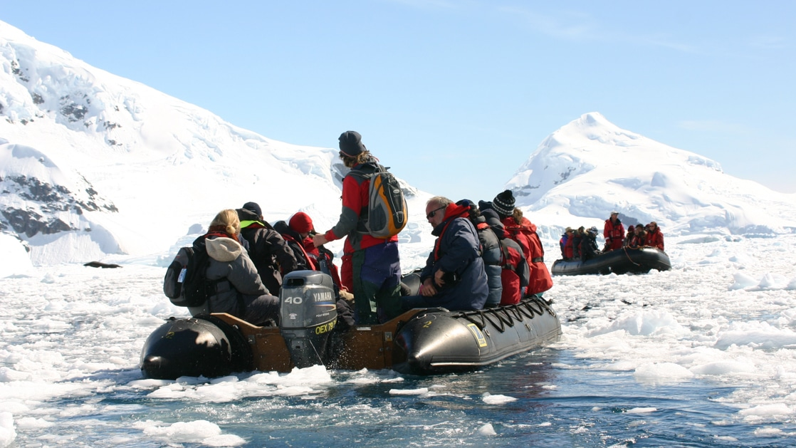 Antarctica travelers in jackets of various bright colors sit in a Zodiac as it cruises amongst icebergs on a sunny day.