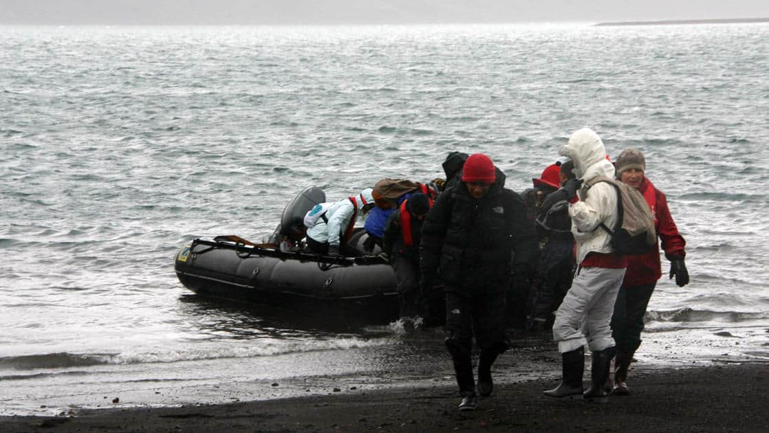 adventure travelers doing a shore landing on a skiff on an overcast day in antarctica