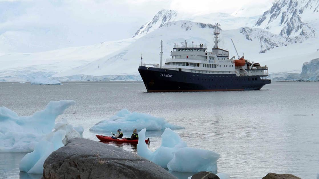 adventure travelers kayak during their antarctica expedition cruise trip, with the plancius ship in the distance
