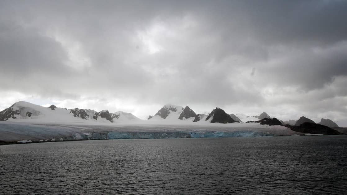 a long line of mountains with dark ocean in the foreground on an overcast day in antarctica