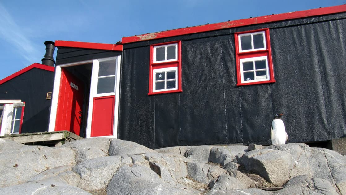 port lockroy antarctica building with black paint and red trim on a sunny day