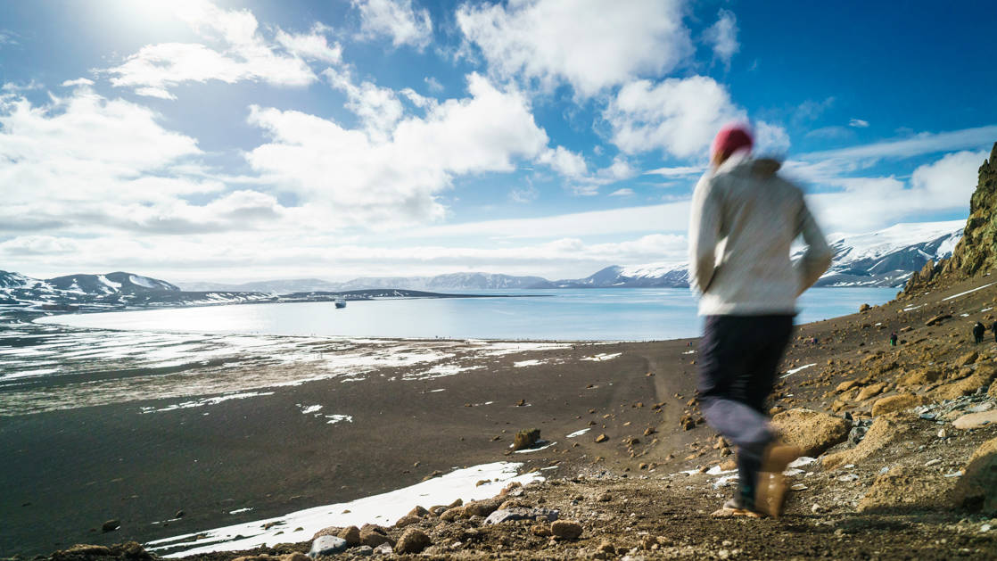 Hiker walking along the Antarctica Peninsula in the South Shetlands islands with sun and clouds.