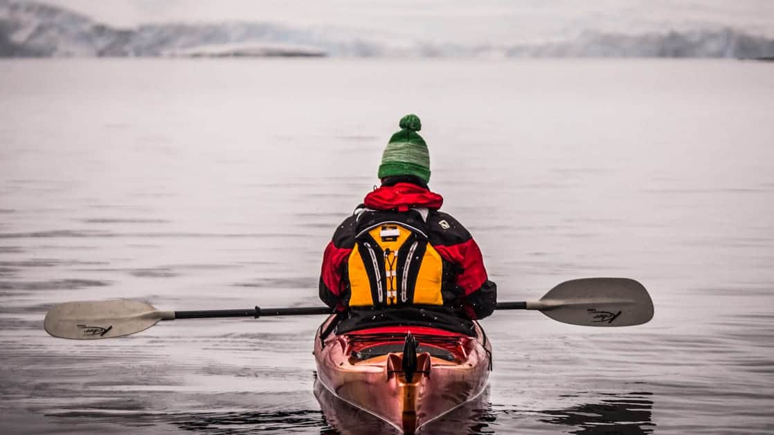 Guest kayaking with beanie with the Antarctic Peninsula in the backgorund