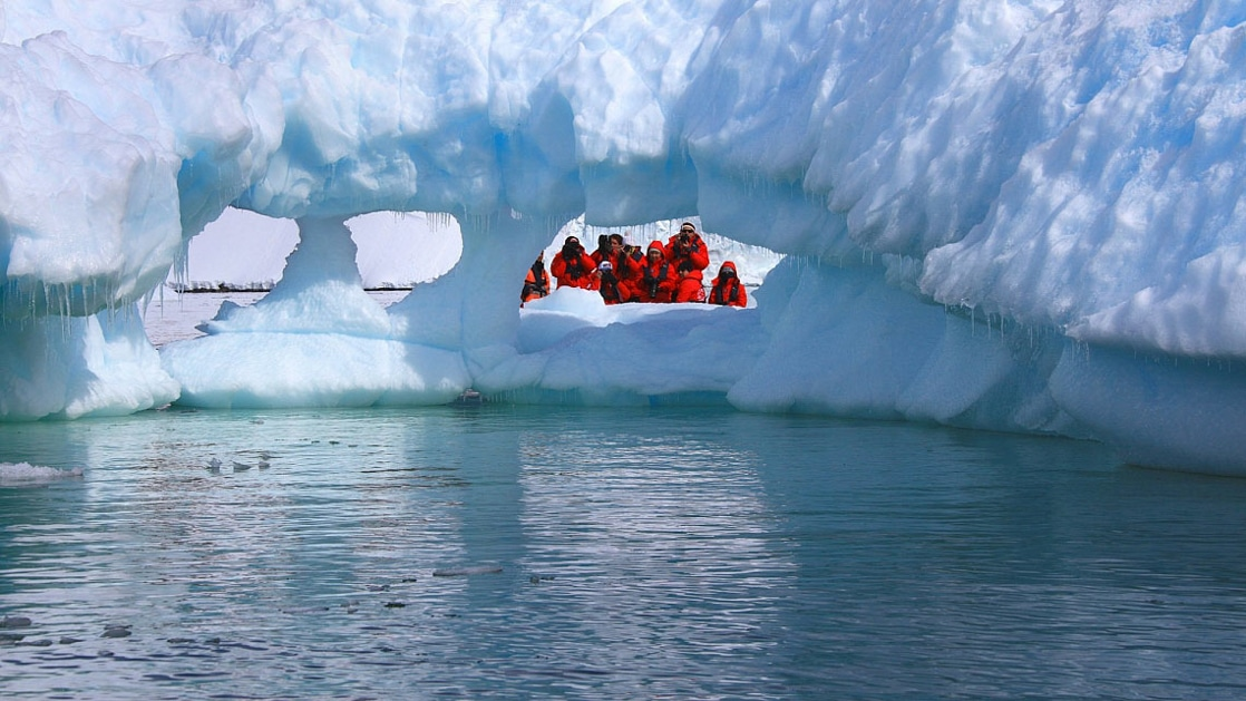 Group of travelers on a small expedition ship in Antarctica wearing their red parkas on a zodiac excursion and looking through one of several holes in an iceberg.