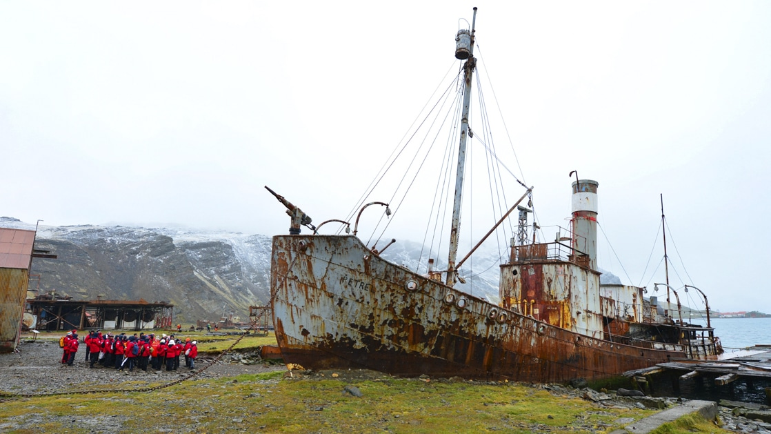 Group of travelers wearing red parks on a land excursion looking up at an abandoned rusty ship in Antarctica.